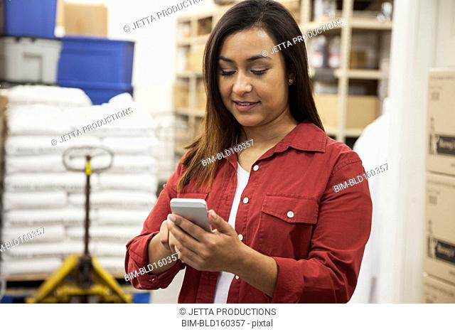 Mixed race worker using cell phone in warehouse