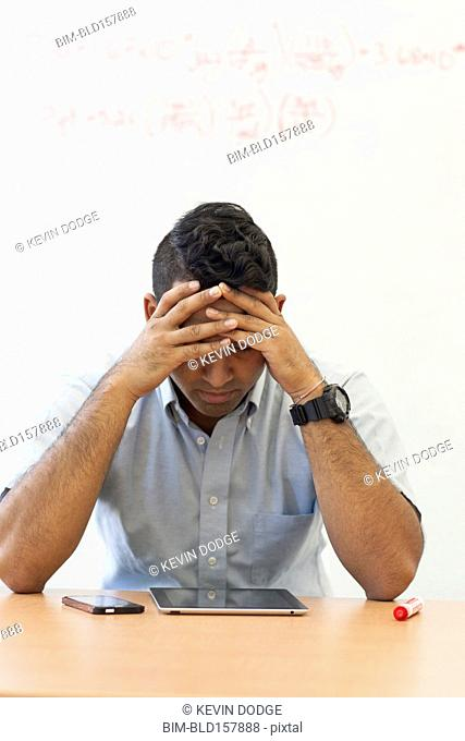 Frustrated Asian businessman with digital tablet and cell phone