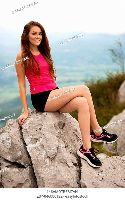 Woman runner resto son a top of a mountain above the valley