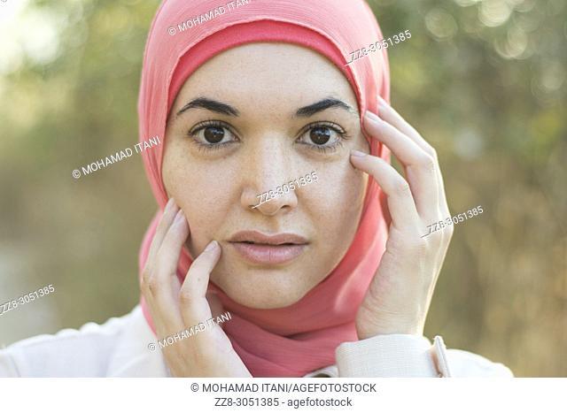 Beautiful Muslim woman wearing Hijab hands touching face