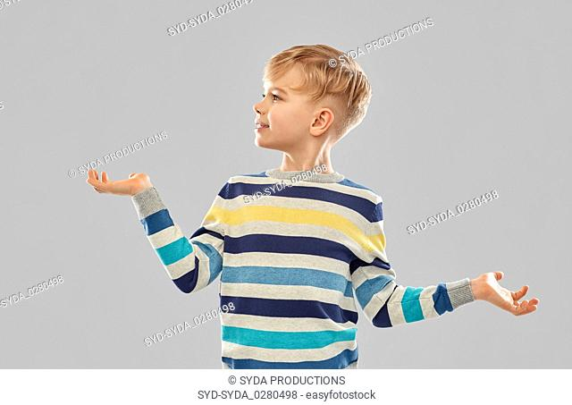 smiling boy holding something on empty hands