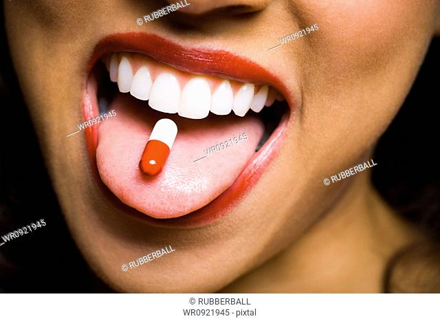 Woman wearing red lipstick with a pill on tongue