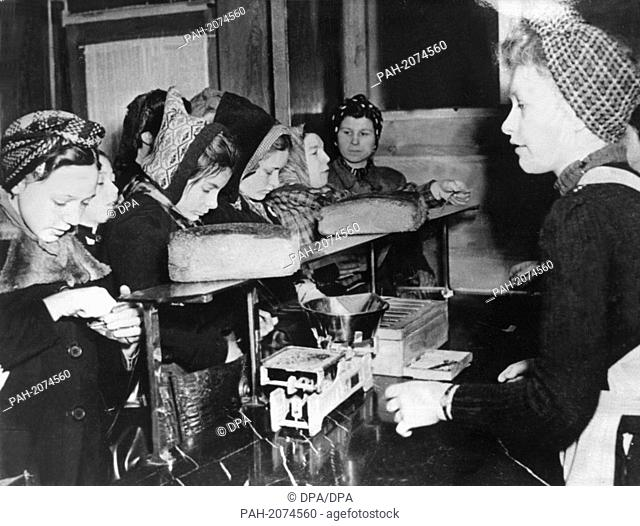 Women are buying fresh bread in a store, during the post-war era in Germany. A young women (l) is searching for her bread stamps