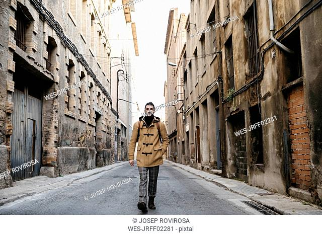 Spain, Igualada, man walking through the industrial zone of the town