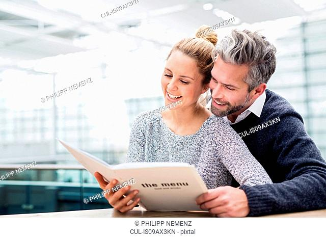 Couple sitting together at table, looking at menu