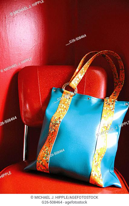 Purse sitting on red chair against a red wall