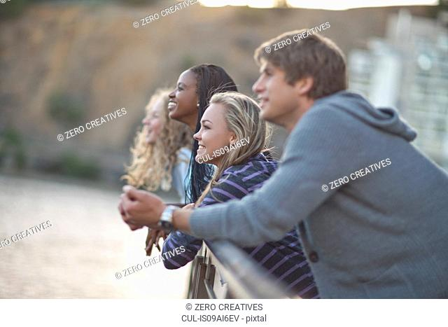 Four young adult friends gazing from riverside railings