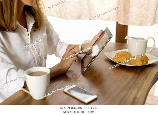 Woman at breakfast table using tablet