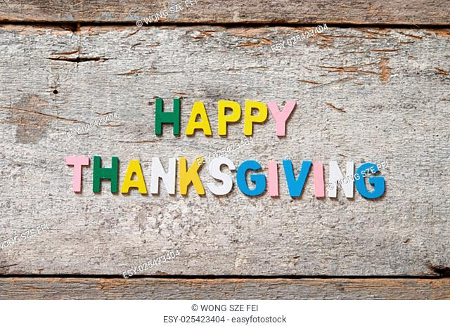 """The colorful words """"""""HAPPY THANKSGIVING"""""""" made with wooden letters on old wooden board"""