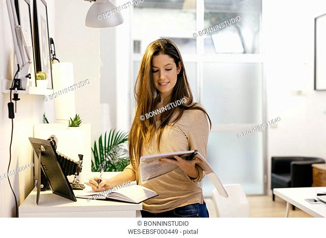 Young female entrepreneur working at home office