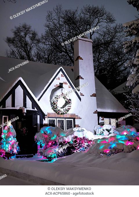 Cute family house decorated with Christmas lights for holidays and covered with snow nighttime scenic. Toronto, Ontario, Canada