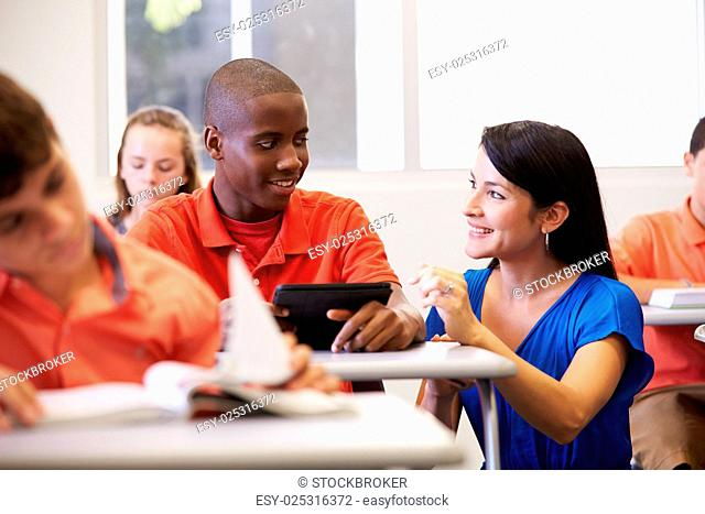 Teacher Helping Male High School Student In Classroom