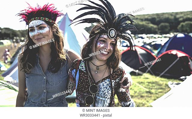 Two smiling young women at a summer music festival face painted, wearing feather headdress, standing among tents