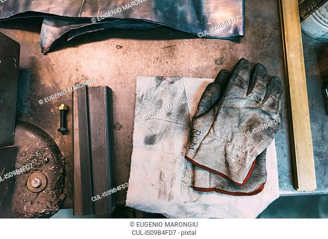 Overhead view of metals and protective gloves on forge workbench
