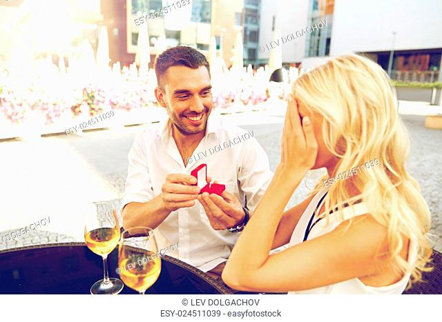 love, anniversary, surprise, people and holidays concept - happy man with engagement ring making proposal to woman at restaurant