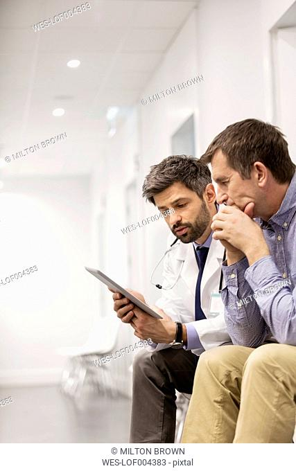 Doctor with digital tablet talking to patient