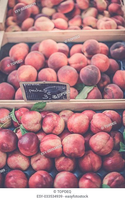 Ripe fresh peaches in a farmers market. Filtered shot with a selective focus