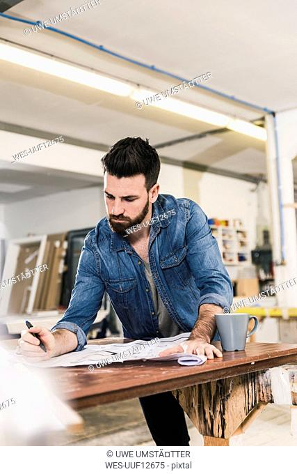 Man looking at draft in workshop