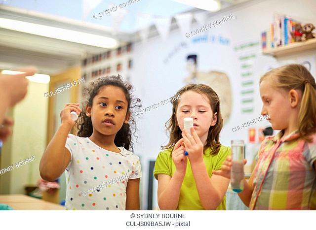 Primary schoolgirls doing experiment in classroom
