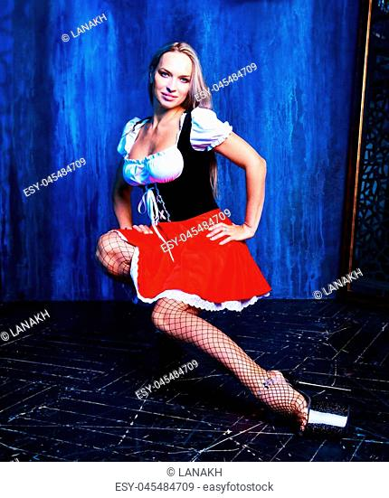 beautiful blond woman wearing a red skirt in the studio