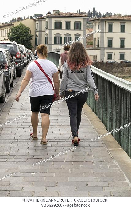 Back view of a young women couple, one with pink hair and a mobile phone in her back pocket, holding hands as they walk across the Santa Trinita Bridge over the...
