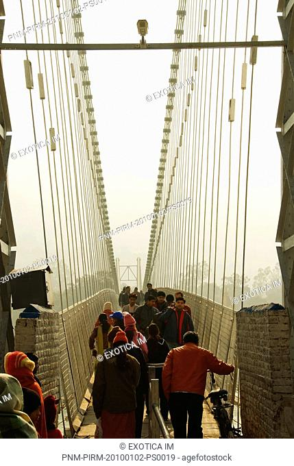 Tourists walking on a suspension bridge, Lakshman Jhula, Ganges River, Rishikesh, Dehradun District, Uttarakhand, India