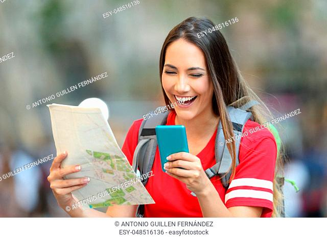 Happy teen tourist laughing using smart phone and holding a paper map on the street
