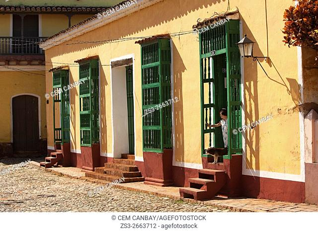 Woman with a dog at the door of a colonial house, near Plaza Mayor-Main Square in the town center, Trinidad, Sancti Spiritu Province, Cuba, West Indies