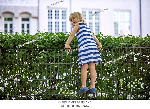 Smuling little girl climbing on fence