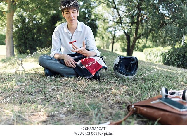 Young man sitting on meadow in park using a fidget spinner
