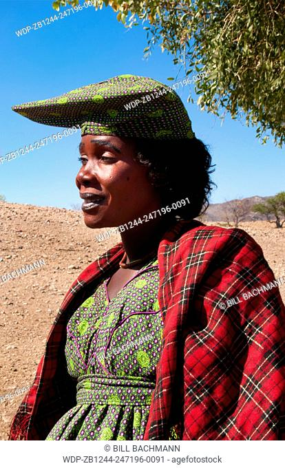 Namibia Africa Northern Desert colorful Herero tribe woman in plaid dress and hat and traditional costume in Tomakas in Puros Conservancy remote village