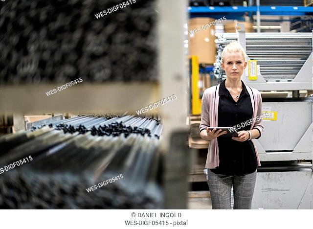 Blond woman holding tablet in high rack warehouse