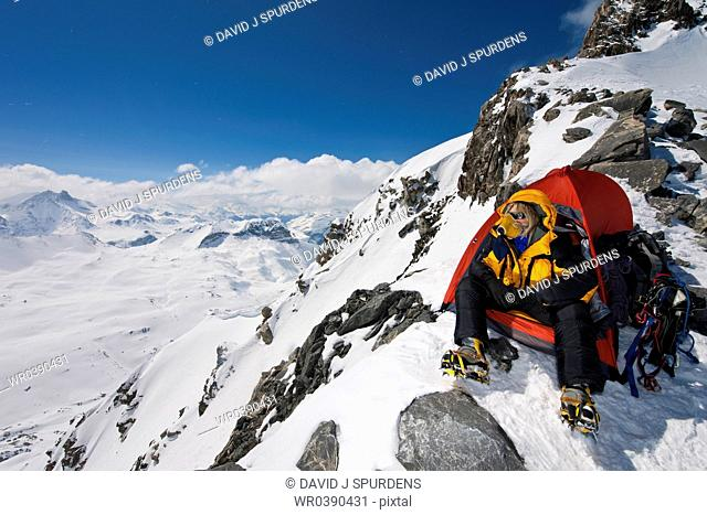 A mountaineer sitting in tent with oxygen mask looks out over high snowy mountains