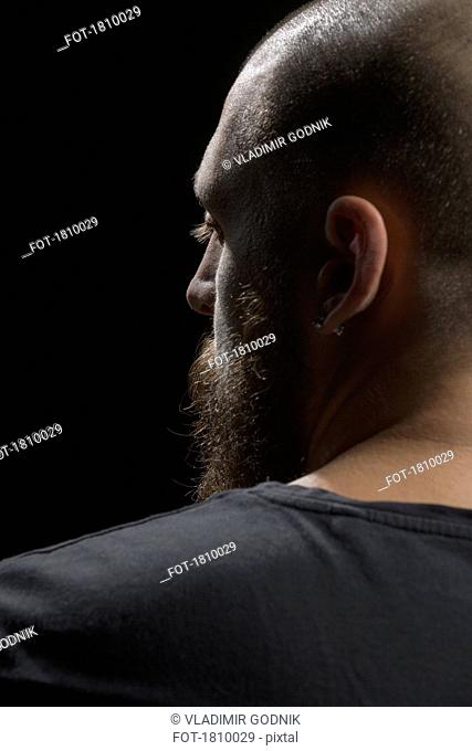 Profile serious man with beard and earring