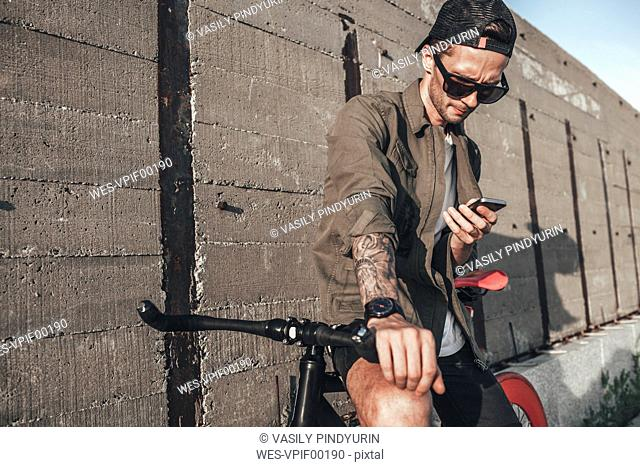 Young man using cell phone on fixie bike