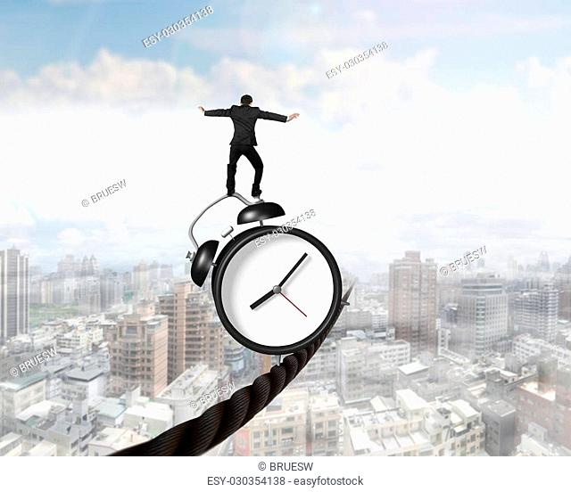 Businessman balancing alarm clock on tightrope, with sky clouds cityscape background