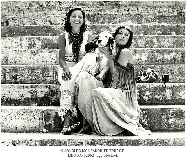 Mia Martini and Loredana Berté with a dog. Italian sisters and singers Mia Martini (Domenica Berté) and Loredana Berté sitting on some steps with a dog