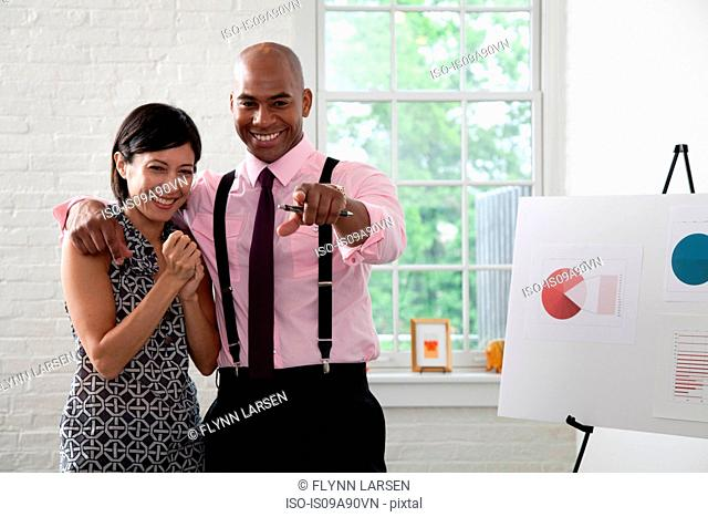 Office colleagues pointing and smiling in meeting