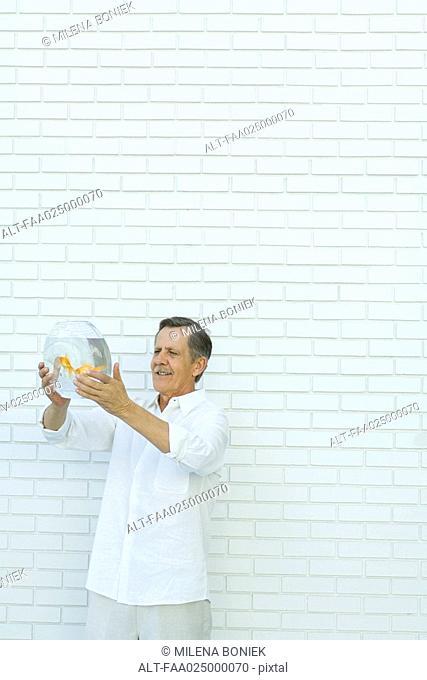 Man holding up goldfish bowl