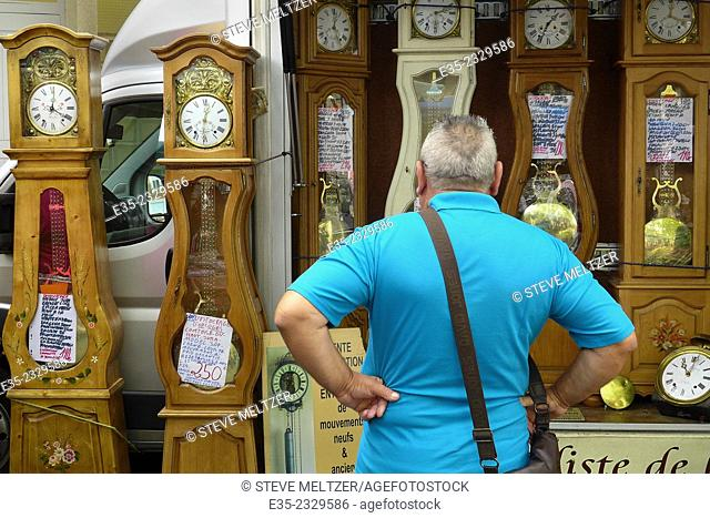 A grandfather looks at grandfather clocks
