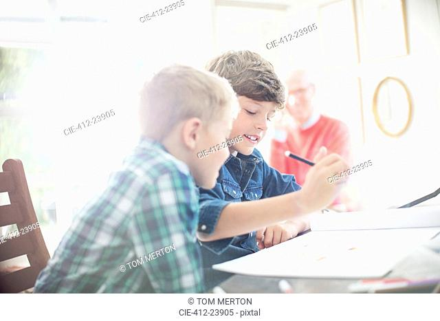 Boys drawing together at table