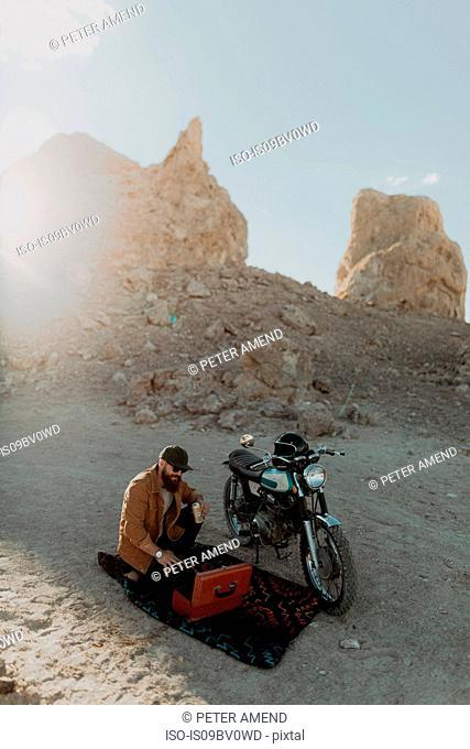 Motorcyclist with toolbox beside bike, Trona Pinnacles, California, US