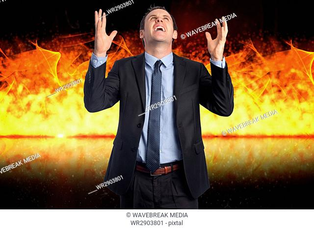Digital composite image of angry businessman with fire in background