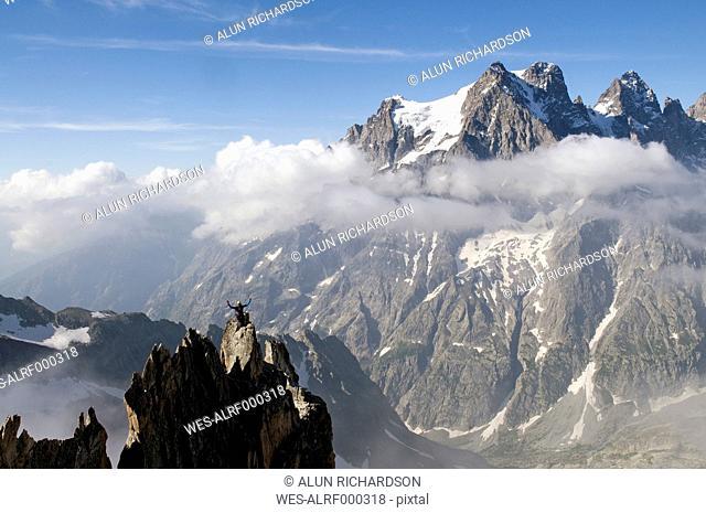 France, Ecrins Massif, Aiguille Noire de Peuterey and Mont Pelvoux, cheering mountaineer on summit