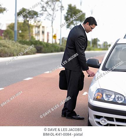 Businessman unlocking a car door