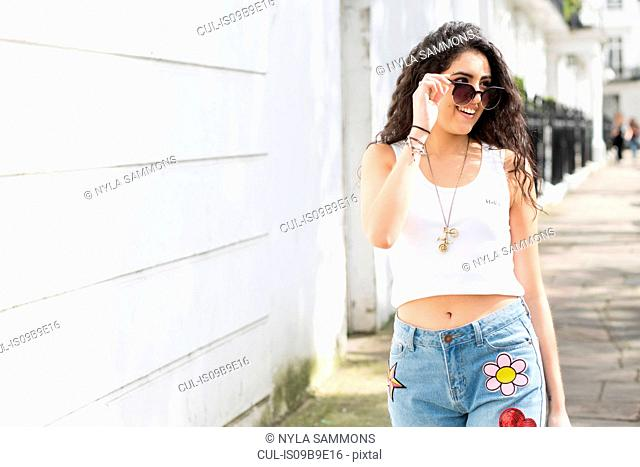 Young woman with long wavy hair strolling on street looking over sunglasses