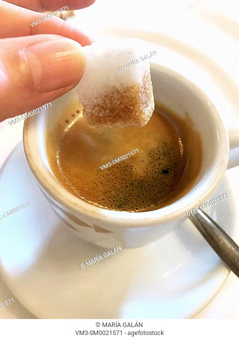 Hand dipping a sugar lump in a cup of coffee. Close view