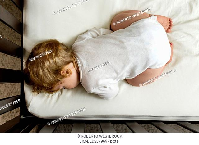 Caucasian baby boy sleeping in crib