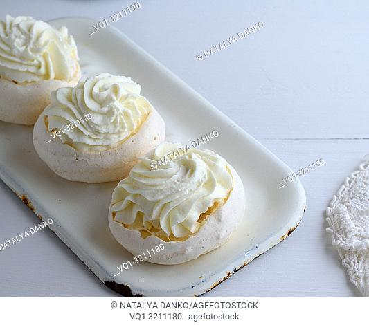 baked round meringue with cream on white iron trays, top view