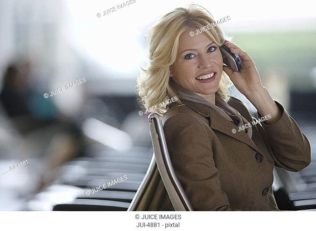 Businesswoman using mobile phone, smiling, side view, portrait